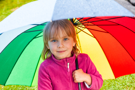 Portrait of jittle girl wearing fleece jacket standing hiding under colorful umbrella in a rain 写真素材 - 122048912