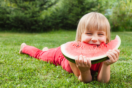 Portrait of happy elementary age girl narrowing her eyes enjoying eating slice of juicy watermelon lying on a meadow in a summer garden