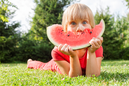Portrait of elementary age girl having fun while eating slice of juicy watermelon lying on a meadow in a summer garden 写真素材