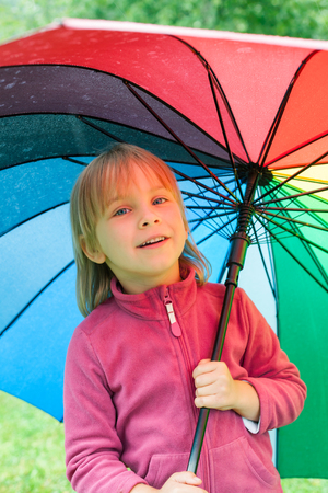 Portrait of jittle girl wearing fleece jacket standing hiding under colorful umbrella in a rain