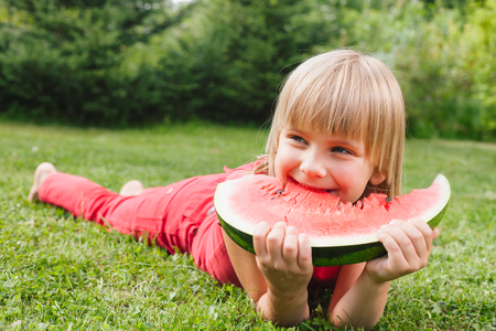 Portrait of happy elementary age girl enjoying eating slice of juicy watermelon lying on a meadow in a summer garden