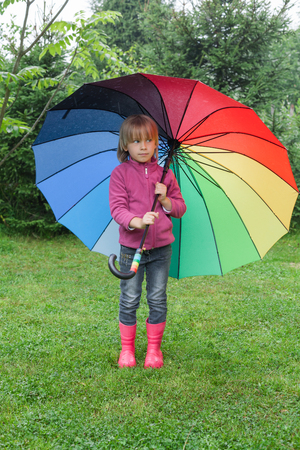 Little girl wearing fleece jacket and rubber boots standing hiding under colorful umbrella in a rain - drizzly weather concept 写真素材
