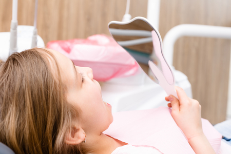 Portrait of elementary age girl sitting in a dental chair inspecting repaired teeth looking thru tooth-shaped mirror in pediatric dental clinic 写真素材