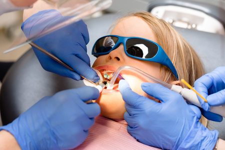 Dentist performing dental procedure to a little girl in pediatric dental clinic with a help of assistant. Calm child is sitting in a dental chair wearing sunglasses 写真素材