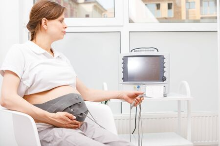 Pregnant woman sitting in clinic performing cardiotocography (CTG). The belt on her belly connected to the Cardiotocograph machine aka Electronic Fetal Monitor (EFM) recording the fetal heartbeat and the uterine contractions during pregnancy