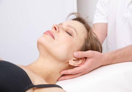 Young woman's neck being manipulated by osteopathic or chiropractic manual therapist