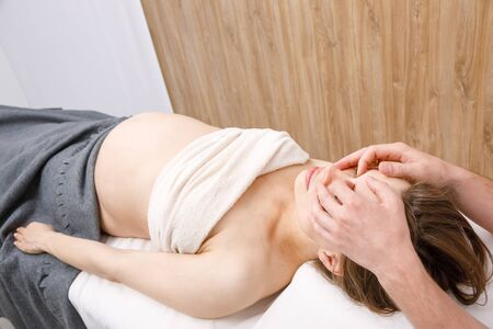 Pregnant woman receiving osteopathic or chiropractic treatment in a clinic. Manual therapist manipulates woman's head Banco de Imagens
