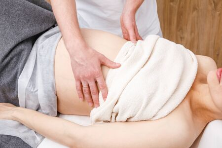 Pregnant woman receiving osteopathic treatment in a clinic. Manual therapist manipulates woman's belly