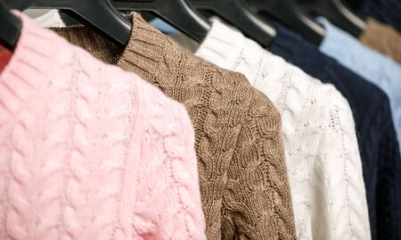 Various cable knit sweaters or pullovers on hanger rack in a clothes store or at a wardrobe, selective focus