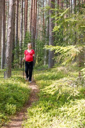 Young pregnant woman walking along a trail through the forest during warm sunny summer day using hiking poles enjoying nature - healthy pregnancy lifestyle concept