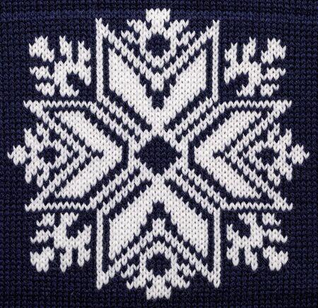 Gros plan d'un ornement de style scandinave en flocon de neige tricoté blanc sur un pull de Noël bleu
