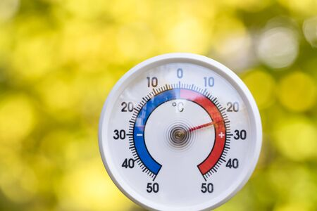Outdoor thermometer with celsius scale showing warm temperature, blurred autumn leaves seen in background - hot indian summer or global warming concept