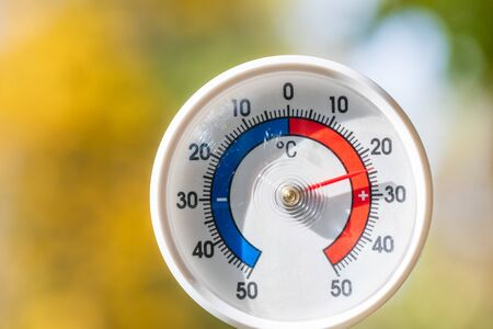 Outdoor thermometer with celsius scale showing warm temperature, blurred autumn leaves seen in background - hot indian summer or global warming concept Stock Photo