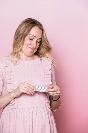 Young pregnant woman wearing pink dress looking at blister pack of medicine tablets in confusion ponders to take pills during pregnancy or not. Studio shot on pink background. Prenatal medication concept