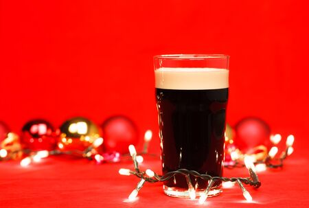 Pint glass of dark beer or stout ale with christmas lights and baubles on red background