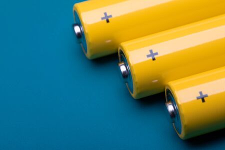 Close up shot of yellow AA alkaline or rechargeable NiMH batteries on blue background, shallow focus