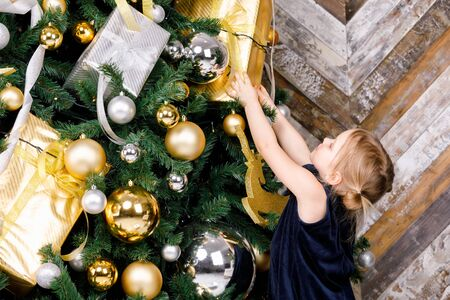 Elementary age girl wearing blue dress pulling hands trying to reaches for wrapped present hanging on christmas tree at home