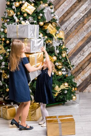 Two sisters wearing blue dresses standing next to the decorated Christmas Tree pulling stack of big wrapped gift boxes cannot share a presents on Boxing Day