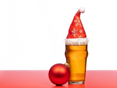 Full pint glass of lager beer or ale with Santa Claus red hat on and christmas bauble on red isolated on white background Stock Photo