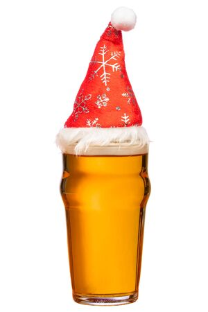 Full pint glass of lager beer or ale with Santa Claus red hat isolated on white background