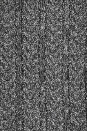Grey melange knitted fabric with cable pattern made of heather mixed yarn background