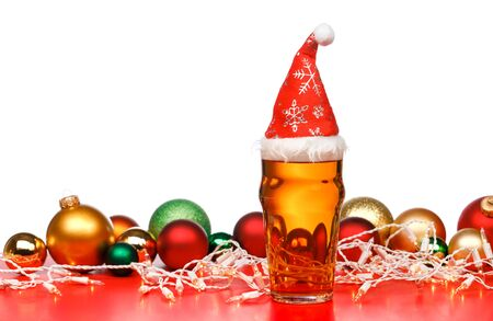 Full pint glass of lager beer or ale with Santa Claus red hat, christmas baubles and lights on red background isolated on white