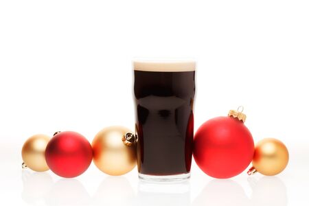 Full pint glass of dark beer or stout ale with christmas baubles on white background
