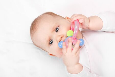 Six month baby girl chewing plastic teething toy lying on her back