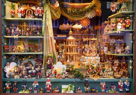 Rothenburg ob der Tauber, Germany - May 9, 2019: Souvenir shop window displaying various bavarian memorabilia: wooden dolls, toy soldiers, kings, figurine incense burners, ceramic houses etc.