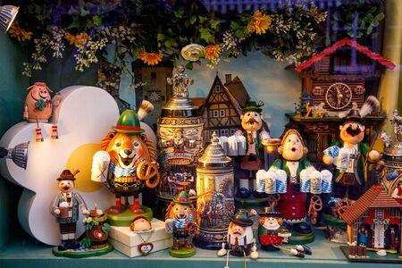 Rothenburg ob der Tauber, Germany - May 9, 2019: Souvenir shop window displaying various bavarian memorabilia: wooden toys, figurine incense burners and traditional ceramic beer mugs Editorial