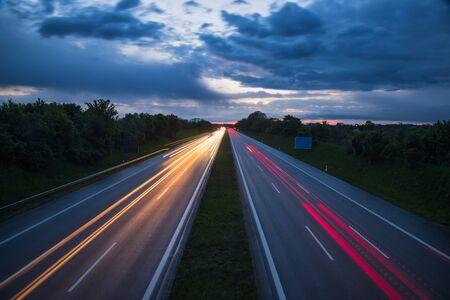 Dramatyczne wieczorne niebo nad autostradą lub autostradą ze śladami światła samochodu w nocy, ujęcie z długim czasem naświetlania