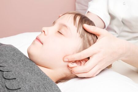Elementary age girl receiving osteopathic or chiropractic treatment in pediatric clinic. Manual therapist manipulates child's scull Banco de Imagens
