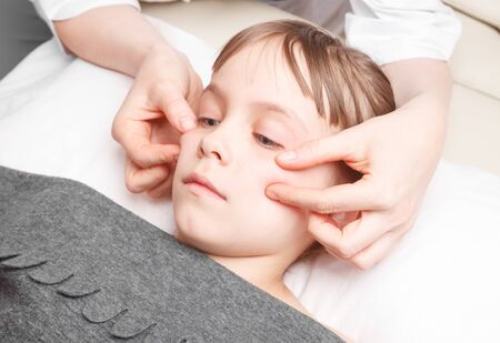 Elementary age girl receiving osteopathic or chiropractic treatment in pediatric clinic. Manual therapist manipulates child's cheeks Banco de Imagens