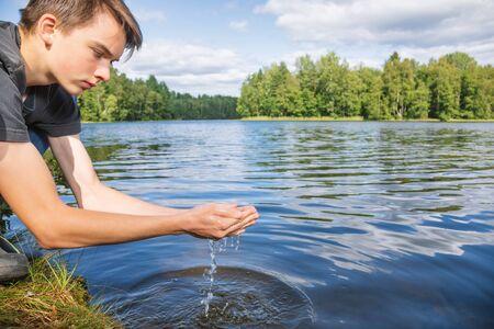 Adolescente recoge agua cruda sin filtrar de un lago. Concepto de fuente de agua natural