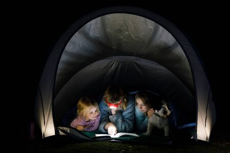 Girls laying in a camping tent wrapped in a sleeping bag with dog reading a book with flashlight at night during summer holidays 스톡 콘텐츠