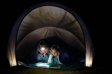 Preteen girls laying in a camping tent wrapped in a sleeping bag reading a book with flashlight at night during summer holidays