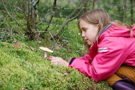 Une fille d'âge primaire a trouvé un champignon potentiellement dangereux en jouant dans une arrière-cour ou en campant dans une forêt - concept de risque d'empoisonnement aux champignons chez les enfants Banque d'images