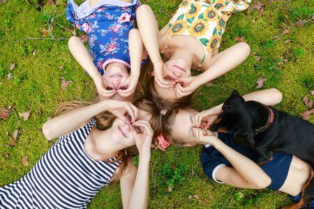 Filles d'âge différent allongées ensemble sur une mousse dans une forêt d'été profitant des vacances d'été en plein air Banque d'images