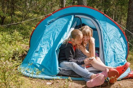Tween girls sitting together in a camping tent using smartphone messaging or checking social media in a summer forest during summer holidays Stockfoto