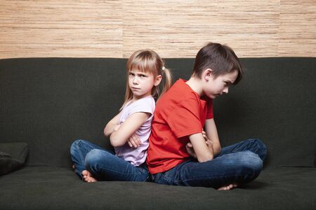 Frustrated siblings sittng on sofa stuck at home during isolation. Quarantine and lockdown protective measures against spreading of coronavirus pandemic disease