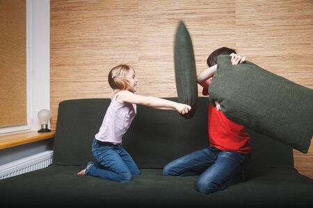 Siblings going mad stuck at home being in self-isolation. Children fighting with pillows on a couch.