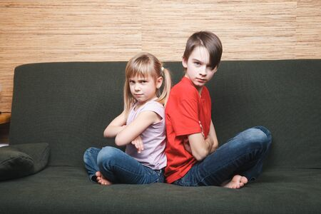 Frustrated siblings sitting on sofa stuck at home being in self-isolation.