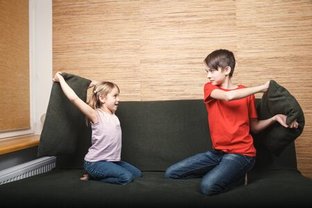 Siblings fighting with pillows stuck at home being in self-isolation. Quarantine and lockdown protective measures against spreading of coronavirus pandemic disease