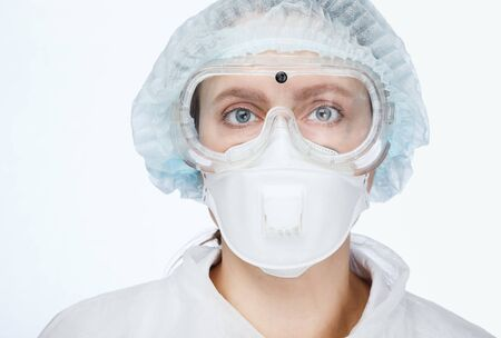 Close-up shot of young female doctor wearing PPE protective suit. Coronavirus COVID-19 outbreak concept