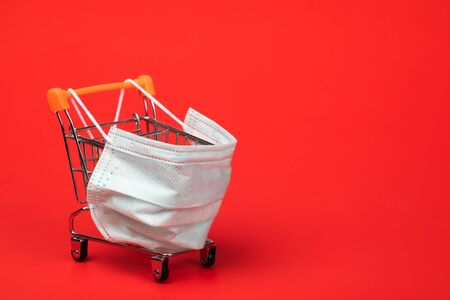 Supermarket cart with protective mask on on red background. Shopping during Coronavirus COVID-19 pandemic outbreak concept