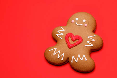 Christmas Gingerbread man sugar cookie in humanoid shape with red heart icing decoration on red background
