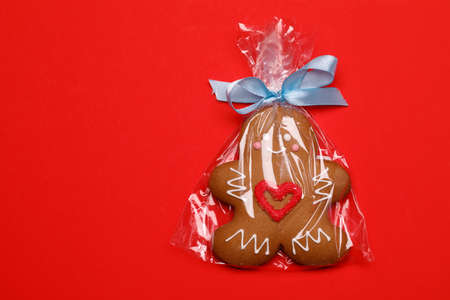 Iced Christmas Gingerbread man sugar cookie with red heart wrapped in plastic on red background
