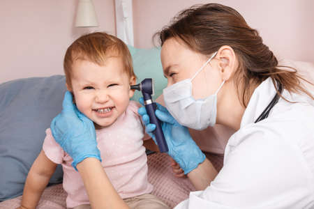 Pediatrician examines ear of baby girl at home during coronavirus COVID-19 pandemic quarantine. Doctor using otoscope (auriscope) to check ear canal and eardrum membrane of a child