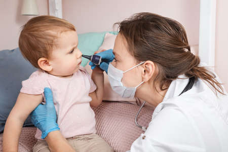 Pediatrician examines nose of baby girl at home during coronavirus COVID-19 pandemic quarantine. Doctor using otoscope (auriscope) to check nasal passage of a child Standard-Bild
