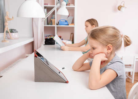 Girls sitting by the desk in the children's room studying at home during Coronavirus COVID-19 quarantine